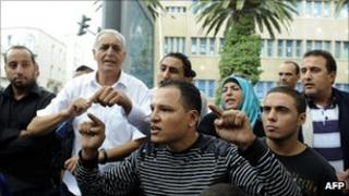 People demonstrate in front of the headquarters of the private TV station Nessma, Tunis, on 9 October 2011