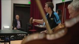 Violinists playing alongside table tennis match