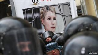Riot police stand guard near a board displaying a portrait of former Ukraine PM Yulia Tymoshenko at a rally in Kiev