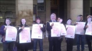 Unison members wearing masks of council executives whose pay is unaffected by the changes to workers contracts outside Birmingham City Council