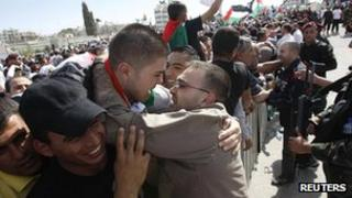 Newly-released Palestinian prisoner (right) greeted by a relative in the West Bank city of Ramallah on 18 October 2011