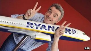 Mr O'Leary smiling with a model of a Ryanair plane