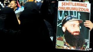 Veiled protesters brandish a poster of the late Chechen warlord Shamil Basayev at a protest outside the Russian consulate in Istanbul, 24 September 2011
