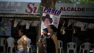 Women pass by the headquarters of a mayoral candidate for the upcoming elections in Puerto Gaitan, Meta department