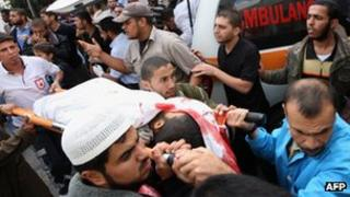 Palestinians carry a militant's body into the al-Najar hospital in the southern Gaza Strip – 29 October 2011