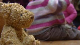 Teddy bear with baby girl in background