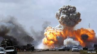 Vehicles belonging to pro-Gaddafi forces explode after a Nato airstrike on a road between Benghazi and Ajdabiyah on 20 March 2011