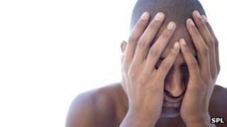 Depressed young man holding his face in his hands