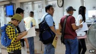 Workers line up at a Philippine Overseas Employment Administration office in Manila on 2 November 2011