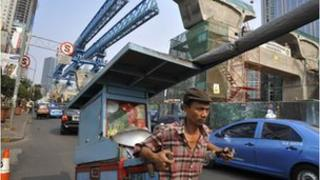 An Indonesian vendor pulls his food cart on the road next to an elevated road construction in central Jakarta.