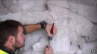 A stonemason carries out repairs at the Royal Artillery Memorial