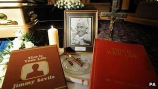 A photo, cigars and This Is Your Life books next to the golden coffin of Sir Jimmy Savile