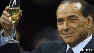 Silvio Berlusconi holds a glass of wine at San Siro stadium in Milan in this September 28, 2008 file photo