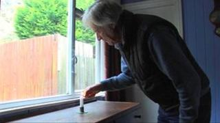 John McCarter lights a candle
