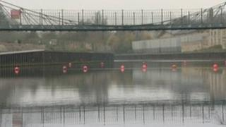 Bright orange buoys stop river traffic from sailing underneath the Victoria Bridge on the River Avon in Bath