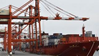 Containers are loaded onto a cargo ship at Tokyo port