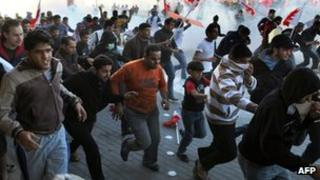 Protesters run from tear gas in the village of Sanabis, near Manama, Bahrain, on 14 February 2011