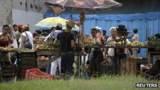 People buy food at a market in Havana on 12 November 2011