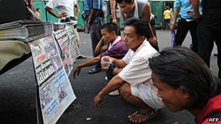 Thai men read newspapers in downtown Bangkok