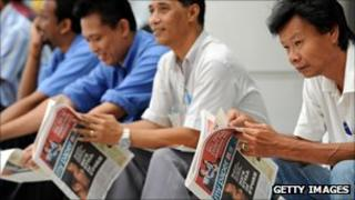 Readers scan the papers in Singapore