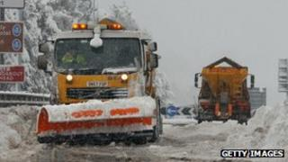 Snow ploughs clear deep snow on a main road in Scotland.