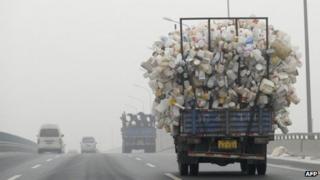 A truck carrying bottles drives in Beijing on 5 December 2011