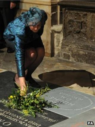 Carol Hughes lays flowers on Ted Hughes's memorial stone