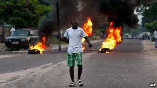 An opposition supporter in front of burning tyres in Kinshasa on 9 December 2011