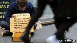 Shoppers walk past a homeless man