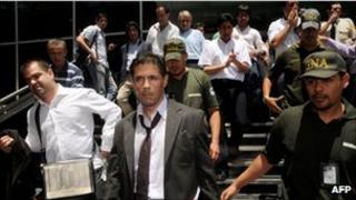 Argentine judge Walter Bento and police officers leaving the offices of Cablevision in Buenos Aires
