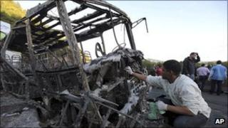 An investigator collects samples from the charred skeleton of a bus in Caracas