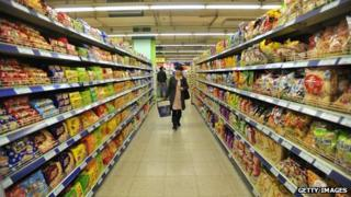 A shopper walks down an aisle in the supermarket