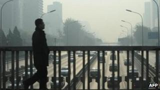 A man walks over the Second Ring Road in Beijing, 22 November 2011