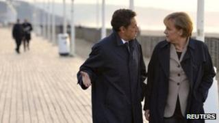 French President Nicolas Sarkozy and German Chancellor Angela Merkel walk near the sea in Deauville, France, October 2010