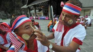This picture taken on January 11, 2011 shows ethnic Karen men applying a traditional tanakha paste to each other as they prepare for a welcoming ceremony organised for leaders of the rebel Karen National Union arriving for talks with a Burmese government delegation