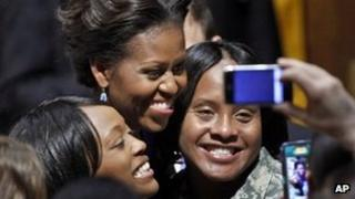 Michelle Obama poses for a photo with US Army Staff Sergeants 11 January 2012