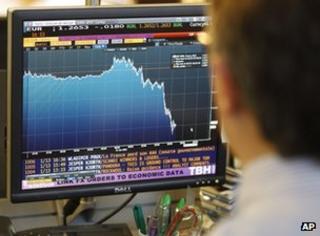 Trader looking at dollar-euro exchange rate graph