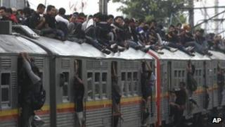 File photo: Passengers on top of a crowded commuter train in Jakarta