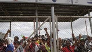 Labourers who were hired to work on the Panama Canal expansion project protest behind a fence in Cocoli on the outskirts of Panama City, 17 January 2012.