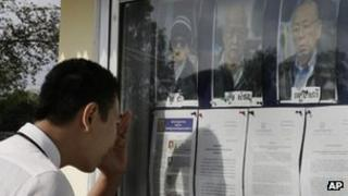 A student reads court documents displaying portraits of Khmer Rouge leaders Ieng Sary, from right, Khieu Samphan and Nuon Chea during a UN-backed war crime tribunal in Phnom Penh, Cambodia, on 16 January, 2012