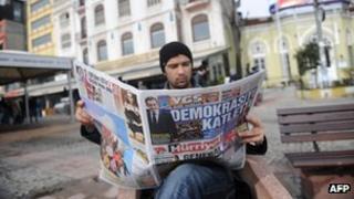 "Man in Istanbul reading Turkish newspaper Hurriyet, showing the headline ""He's slain democracy"""
