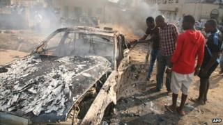 Men look at the wreckage of a car following a bomb blast carried out by Boko Haram at St Theresa Catholic Church outside the Nigerian capital, Abuja, on 25 December 2011