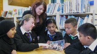 A teacher works with younger pupils
