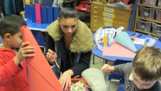 Teenager helps toddlers make paper hats