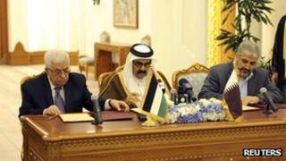 Palestinian President Mahmoud Abbas (L) and Hamas leader Khaled Meshaal (R) sit on either side of Qatar's Emir Sheikh Hamad bin Khalifa al-Thani as they sign an agreement in Doha