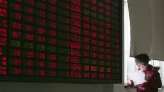 An investor looks at a document next to the stock price monitor at a private securities company Friday Jan. 20, 2012 in Shanghai, China