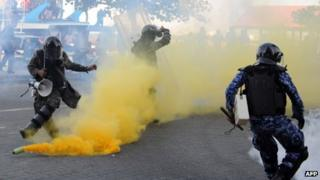 Maldivian policemen try to take cover as anti-government demonstrators throw back a teargas canister in the capital island Male on February 8, 2012