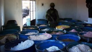 A soldier stands guard next to barrels of drugs seized in Mexico