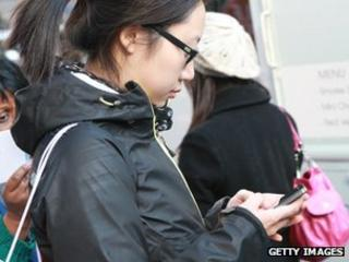 A woman sends a message on her smartphone