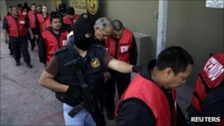 Detained prison guards are led away by a masked policeman after being presented to the media